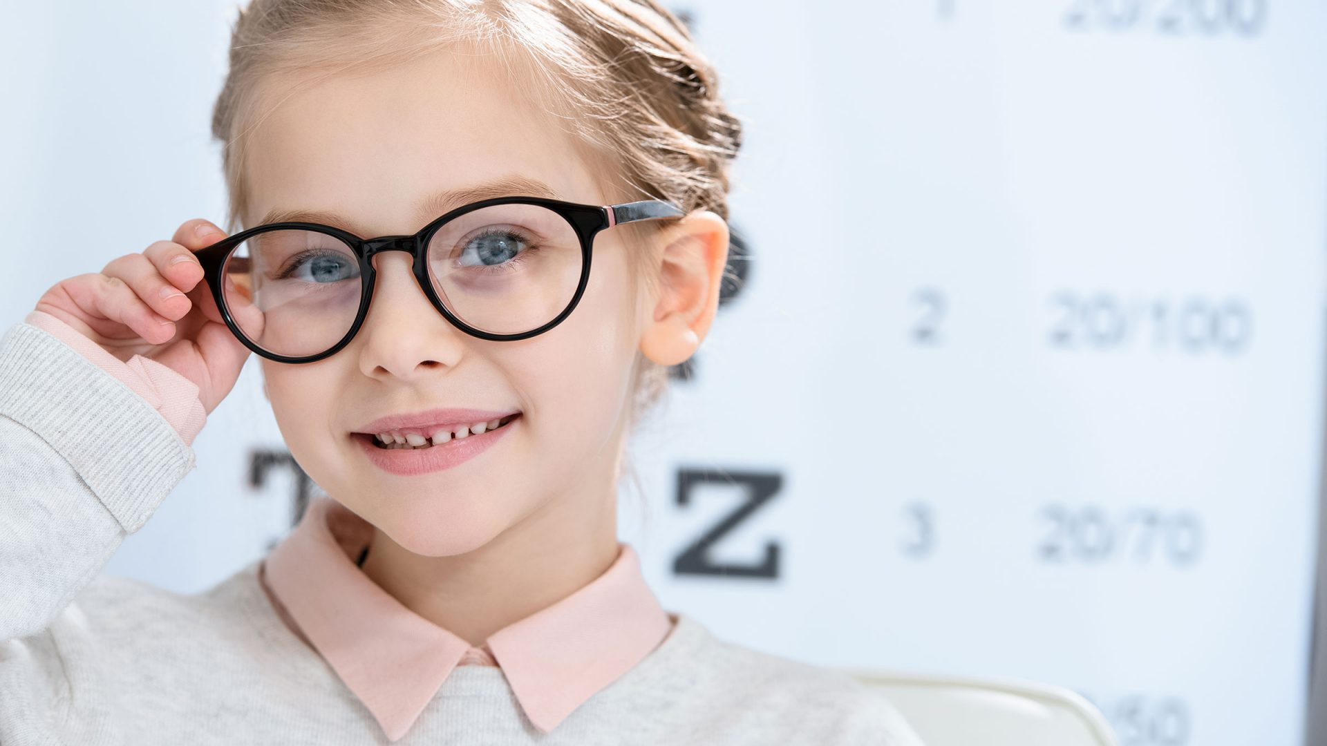 young girl with nice glasses standing near an eye chart