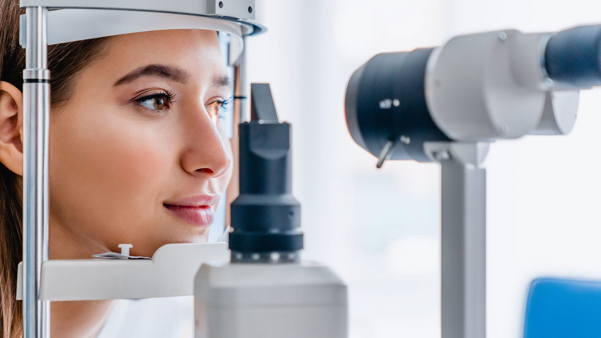 woman having her eyes examined using optometry equipment